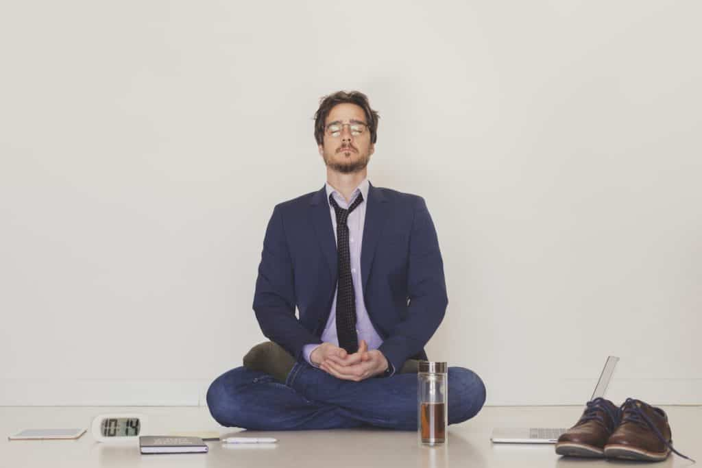 A handsome man wearing a suit and a tie meditating on the floor
