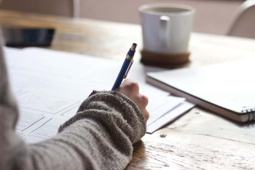 A cropped image of a person holding a pen while writing with a coffee mug in the background